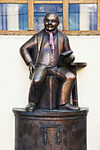 'Bronze statue of a man sitting and holding a book; Bayern, Germany'