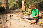 'A tourist plays with the wild monkeys that live in the Monkey Forest, located in the Xe Champhone region; Laos'
