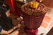 'Chinese young woman trying the traditional roll of fortune in a Buddhist temple; Shanzidou, Kinmen Island, Taiwan'