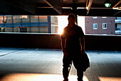 'A young man stands in an elevated parking lot backlit by the setting sun in an urban area; Burlington, Vermont, United States of America'