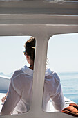 'A woman in a white shirt sits at the front of a boat with a view of the ocean; Ixtapa-Zihuatanejo, Guerrero, Mexico'