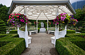 'White gazebo with hanging flower baskets in Minter Gardens; Rosedale, British Columbia, Canada'