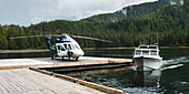 'Helicopter on a dock alongside a fishing boat; Queen Charlotte Islands, British Columbia, Canada'