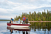 'A family fishing from their motorboat on a calm lake in Northern Ontario; Ontario, Canada'