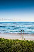 'A couple walks along the popular tourist beach; Poipu, Kauai, Hawaii, United States of America'
