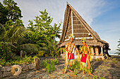 'These two young boys in traditional outfits for cultural ceremonies are standing in front of a Men's House; Yap, Micronesia'
