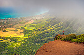 'A man standing on the edge of a cliff on the Kuliouou Ridge Trial enjoys the view of Oahu's windward side and the town of Waimanalo as the clouds roll in on a summer's day; Waimanalo, Oahu, Hawaii, United States of America'
