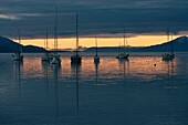 Sunset over the water with sailboats moored in the foreground, Ushuaia, Patagonia, Argentina