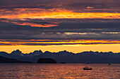 Scenic sunset view of Favorite Passage, Chilkat Mountains, and a silhouetted fishing boat, Inside Passage, Southeast Alaska