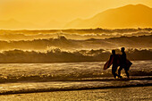 Body surfers walk in the water on the coast of Kodiak Island during late afternoon, Pasagshak State Park, Kodiak Island, Alaska