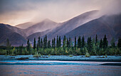 Rain and snow squalls race over the mountains during sunset on the Kelly River, in the western Brooks Range of Noatak National Preserve, Alaska, USA.