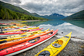 Kayaks in a row on shore at Eklutna Lake, Chugach Mountains, Southcentral Alaska.