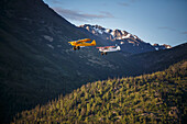 Super Cub airplanes fly over the Turnagain Arm area with Chugach Mountains in the background, Southcentral Alaska