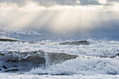 Rough waves along a beach in Homer in Winter with sun rays overhead, Kachemak Bay, Kenai Peninsula, Southcentral Alaska