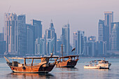 contrast between the traditional boats or qatari dhows at dock and the modern buildings in the skyline of the west bay city center, doha, qatar, persian gulf, middle east