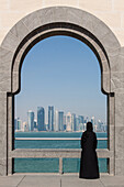 young qatari woman in traditional dress looking at the buildings of the city center from one of the terraces of the museum of islamic art, built by the architect ieoh ming pei, doha, qatar, persian gulf, middle east