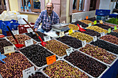 vendor in front of his olive stall, food market of namik kemal, cunda alibey, the olive riviera, north of izmir, turkey