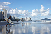 Surfer on the beach in front of apartment buildings, Praia das Asturias, city beach, in Guaruja, Costa Verde, Sao Paulo, Brazil