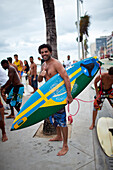 Santos is half Swedish, standing on the boardwalk after surfing, Avenida Oceanica, Barra, Salvador de Bahia, Bahia, Brazil