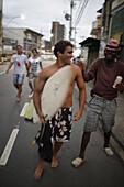 Surfers in the evening, coming from the beach on Avenida Oceanica, Barra, Salvador de Bahia, Bahia, Brazil