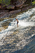 Waterfall surfer, stone slide at river Rio Ribeirao do Meio, men from the village sliding down rocks in bare feet, near Lencois, the main town, starting point to Chapada Diamantina National Park, Bahia, Brazil
