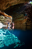 Visitors snorkelling in Poco Azul, sunbeam, underground river, archaeological site, east of the Chapada Diamantina National Park, Andarai, Bahia, Brazil