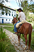 Gaucho, offers horse riding for guests of Fazenda Catucaba, old farm from 1850 is now also a luxurious hotel, located in the coastal mountains, Parque Serra do Mar in Sao Luiz do Paraitinga, Sao Paulo, Brazil
