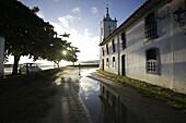 Morning sun in the rain filled Rua de Chapala, curch Iglesia de Nostra Senora das Dores, historic old town, Paraty, Costa Verde, Rio de Janeiro, Brazil
