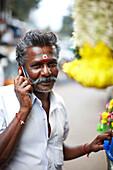 Hindu, customer at a flower stall, market in Valparai, Tamil Nadu, Western Ghats, India