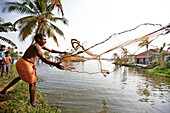Sajeew a fisherman and farmer, throwing out his fishing net (Vishiwala), behind him his sons on small islands in the backwaters, village of Kainakarey, southeast Aleppey, Backwaters, Kerala, India