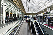 Europe, France, Paris illuminated hall of the Gare de Lyon, A large canopy, an escalator, ramp, many travelers waiting
