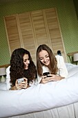 2 teens playing with their mobile phone on a bed