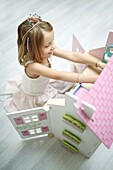 A 5 years old girl dressed like a princess playing with her dollhouse