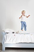 Little boy jumping on his bed