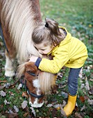 A little girl kissing a pony while he is grazing