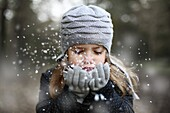 Girl holding snow in her hands