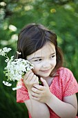 A 5 years old girl with flowers in the countryside