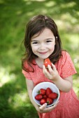 A 5 years old girl eating  strawberries in the countryside