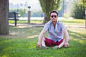 Caucasian man sitting in grass in park