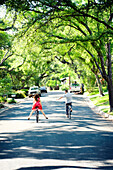 Caucasian children riding bicycles on suburban neighborhood street