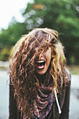Shouting Middle Eastern woman tossing her hair outdoors