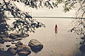 Caucasian girl standing in remote lake