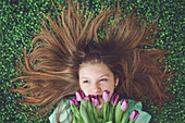 Caucasian girl with tulips laying in grass