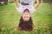 Caucasian girl hanging upside down in backyard