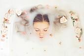 Caucasian teenage girl floating in milk bath with flowers