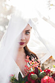 Caucasian bride holding bouquet under veil
