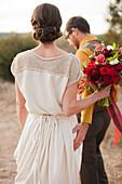 Bride and groom walking on rural hilltop