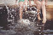 Caucasian girls splashing in lake from wooden dock