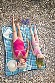 Caucasian grandmother and granddaughter sunbathing on beach