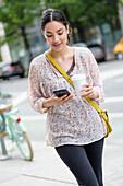 Hispanic woman using cell phone on city sidewalk
